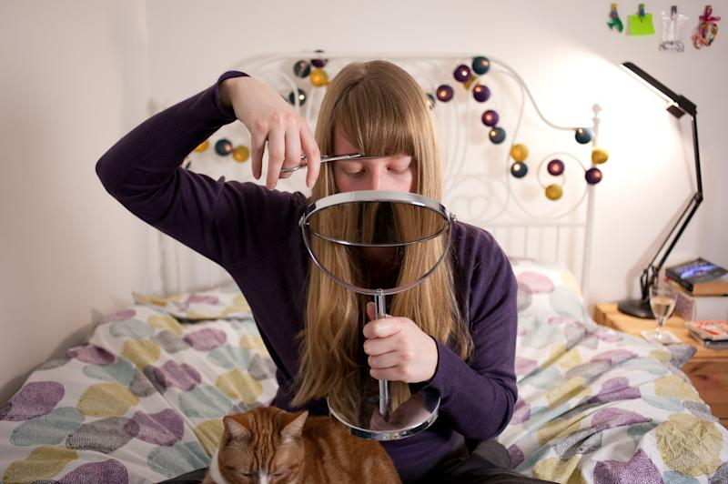 A young blonde woman cuts her hair at home using a hand mirror. She sits on her bed with her pet cat sitting on her lap.