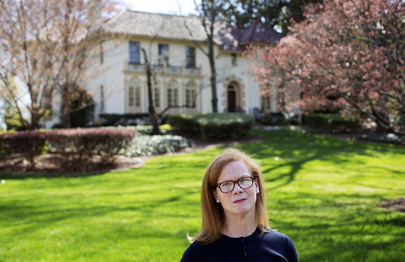 In this March 31, 2014 photo, Laura Mullins, a parishioner of Christ the King Cathedral, stands for a photo outside the former residence of Atlanta Archbishop Wilton Gregory, which will now be used as the church's rectory in Atlanta. Gregory apologized for spending $2.2 million on a mansion for his own personal use. The apology came after Pope Francis permanently removed a German bishop for his lavish spending on a renovation project. Mullins arranged a meeting with Gregory in January during which she and nine other Catholics asked him to sell the new mansion. (AP Photo/David Goldman)