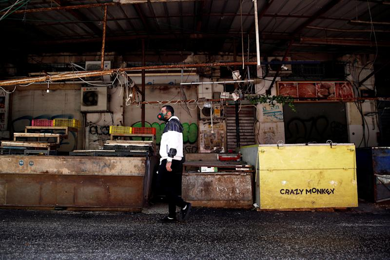 FILE PHOTO: A man wearing a face mask walks past shuttered stalls at a market as Israel tightened a national stay-at-home policy with guidelines aimed at halting the spread of the coronavirus, in Tel Aviv, Israel