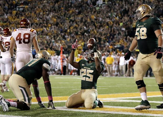Baylor running back Lache Seastrunk (25) celebrates his touchdown as Kelvin Palmer, left, and Spencer Drango, right, watch in the first half of an NCAA college football game against Iowa State, Saturday, Oct. 19, 2013, in Waco, Texas. (AP Photo/Tony Gutierrez)