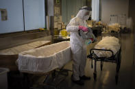 A mortuary worker disinfests the body of a person who died of COVID-19 ahead of a funeral at Memora mortuary in Girona, Spain, Thursday, Feb. 4, 2021. Spain's health ministry said Wednesday that the southern European nation has surpassed 60,000 fatalities from COVID-19. The ministry reported 565 new deaths in the previous 24 hours, taking the total death count since the start of pandemic to 60,370. (AP Photo/Emilio Morenatti)