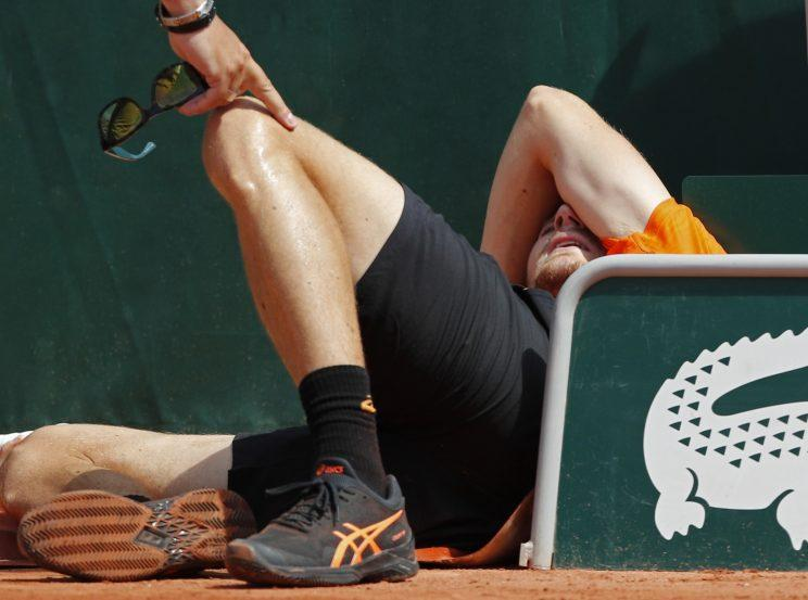 David Goffin lays on the clay after tripping over a rolled-up tarp. (AP)