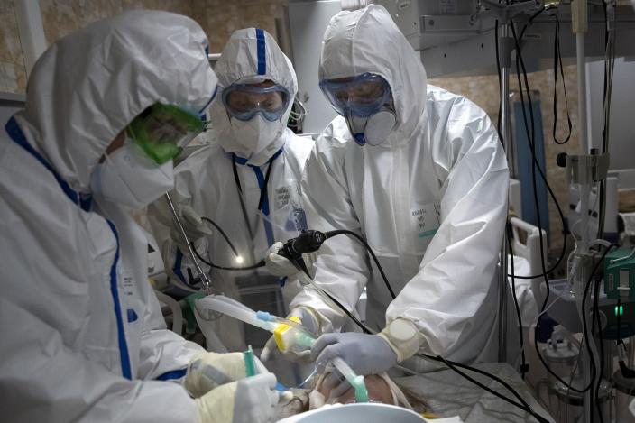 In this photo taken on Friday, May 15, 2020, Dr. Osman Osmanov, right, and Dr. Konstantin Glebov, center left, and Dr. Vitaly Mushkin perform tracheal intubation of a coronavirus patient on artificial lung respiration at an intensive care unit of the Filatov City Clinical Hospital in Moscow, Russia. Moscow accounts for about half of all of Russia's coronavirus cases, a deluge that strains the city's hospitals and has forced Osmanov to to work every day for the past two months, sometimes for 24 hours in a row. (AP Photo/Pavel Golovkin)