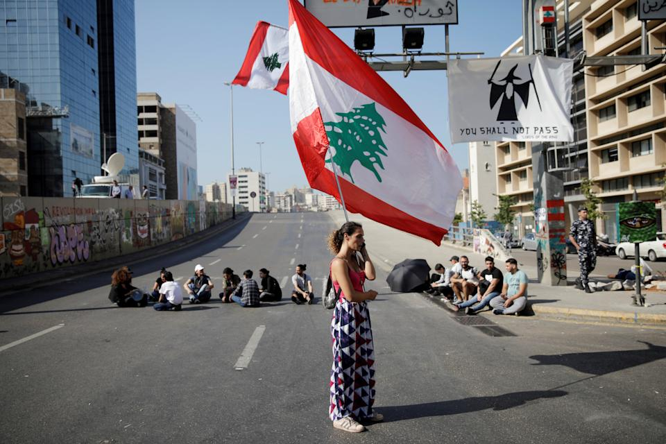 A woman holds a Lebanese flag as she stands at a roadblock during ongoing anti-government protests in Beirut, Lebanon November 4, 2019. REUTERS/Andres Martinez Casares     TPX IMAGES OF THE DAY