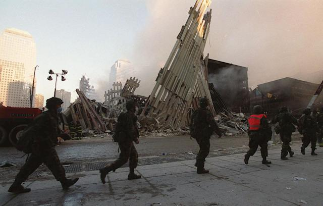<p>National Guardsmen march past the wreckage of the World Trade Center towers in New York, Sept. 13, 2001. (Photo: Stephen Chernin/AP) </p>