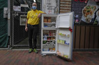 Ahmed Khan poses with a refrigerator at Woosung Street in Hong Kong's old-school neighborhood of Jordan Wednesday, Nov. 18, 2020. Khan, founder of a sports foundation on the same street, said he was inspired to create a community refrigerator after seeing a film about others doing the same thing. He found the refrigerator at a nearby refuse collection point and painted it blue. (AP Photo/Vincent Yu)