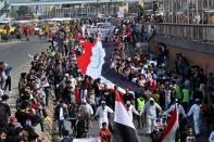 Students and other demonstrators hold national flags during ongoing anti-government protests, in Baghdad, Iraq, Sunday, Feb. 23, 2020. (AP Photo/Khalid Mohammed)