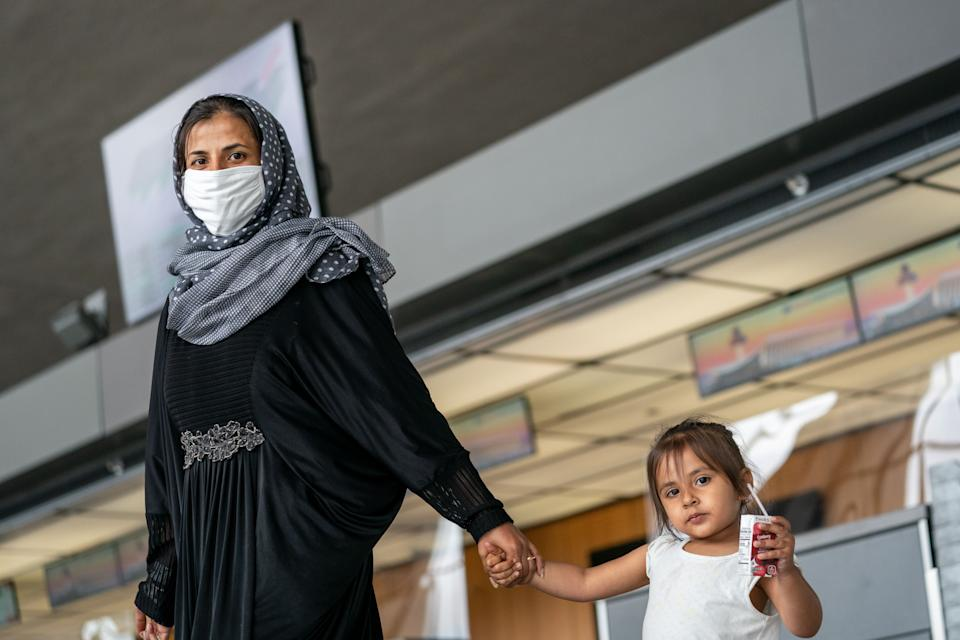 Evacuees who fled Afghanistan walk through the terminal to board buses that will take them to a processing center at Dulles International Airport on Sunday, Aug. 29, 2021. (Kent Nishimura / Los Angeles Times via Getty Images)