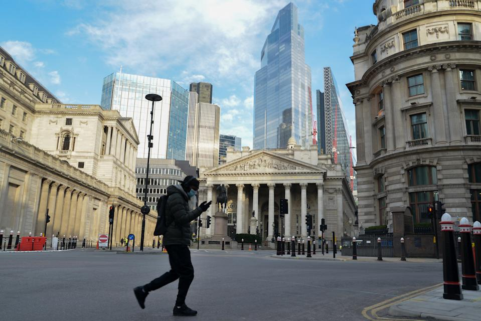 LONDON, UNITED KINGDOM - 2021/02/11: A man wearing a facemask as a precaution against the spread of covid 19, walks across the street opposite the Bank of England. (Photo by Thomas Krych/SOPA Images/LightRocket via Getty Images)