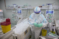 A member of the medical staff prepares to shave a patient in the COVID-19 ICU unit of the Marius Nasta National Pneumology Institute in Bucharest, Romania, Thursday, Sept. 23, 2021. Daily new coronavirus infections in Romania, a country of 19 million, have grown exponentially over the last month, while vaccine uptake has declined to worrying lows. Government data shows that 91.5% of COVID-19 deaths in Romania between Sept. 18-23 were people who had not been vaccinated. (AP Photo/Vadim Ghirda)
