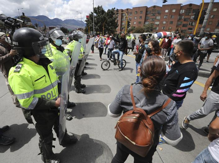 Police face off with merchants blocking a street protesting for the right to work under lockdown, in Bogota, Colombia, Friday, April 16, 2021. A lockdown was reimposed for the weekend after a spike in COVID-19 cases in the Colombian capital, the pandemic's third peak so far. (AP Photo/Fernando Vergara)