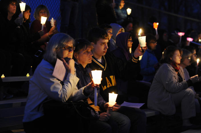 People raise candles as they listen to Maren Sanchez sing during a vigil for her at Jonathan Law High School, Monday, April 28, 2014, in Milford, Conn. Sanchez was fatally stabbed inside the school on Friday hours before her junior prom. (AP Photo/Jessica Hill)
