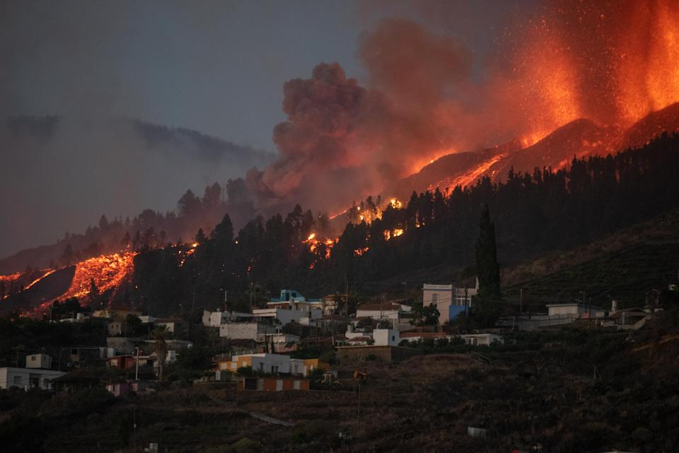 A river of lava approaches houses as Mount Cumbre Vieja erupts in El Paso, spewing out columns of smoke, ash and lava as seen from Los Llanos de Aridane on the Canary island of La Palma on September 19, 2021. - The Cumbre Vieja volcano erupted on Spain's Canary Islands today spewing out lava, ash and a huge column of smoke after days of increased seismic activity, sparking evacuations of people living nearby, authorities said. Cumbre Vieja straddles a ridge in the south of La Palma island and has erupted twice in the 20th century, first in 1949 then again in 1971. (Photo by DESIREE MARTIN / AFP) (Photo by DESIREE MARTIN/AFP via Getty Images)