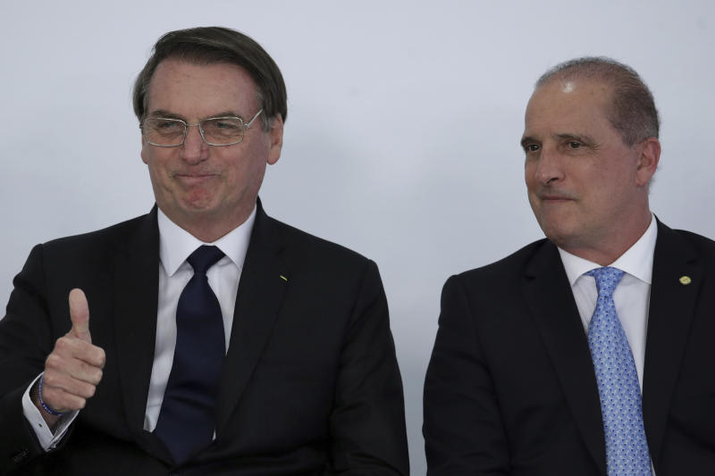 "Brazil's President Jair Bolsonaro, left, gives a thumbs up sign as he stands next to his Chief of Staff Onyx Lorenzoni, during ceremony at the Planalto Presidential Palace in Brasilia, Brazil, Monday, March 25, 2019. Brazil's president says he is ""open to dialogue"" about an ambitious pension reform that has become a central pillar of his administration's agenda. (AP Photo/Eraldo Peres)"