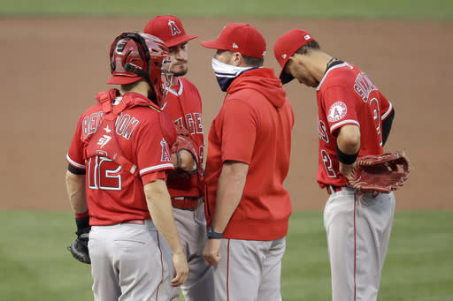 Los Angeles Angels pitcher Andrew Heaney, second from left, speaks with pitching coach Mickey Callaway, second from right, in the first inning of a baseball game against the Oakland Athletics Friday, Aug. 21, 2020, in Oakland, Calif. (AP Photo/Ben Margot)