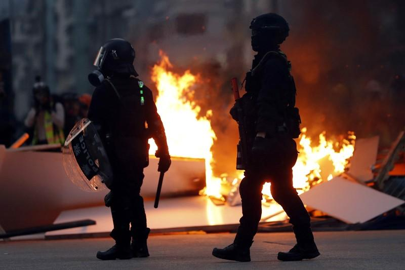 Police officers stand next to a burning barricade during an anti-government protest in Hong Kong China