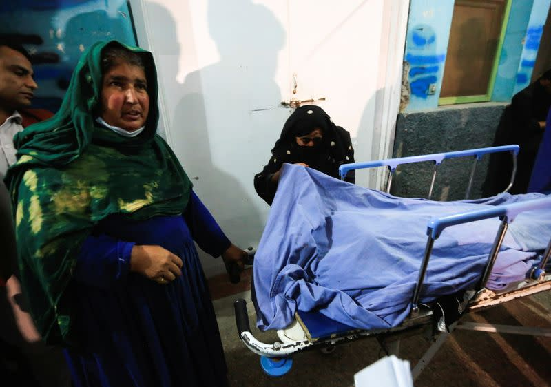 Relatives stand near the body of one of three female media workers who were shot and killed by unknown gunmen, at a hospital in Jalalabad