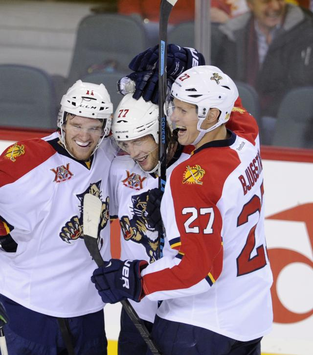 Florida Panthers' Tom Gilbert, center, celebrates his goal against the Calgary Flames with teammates Jonathan Huberdeau, left, and Nick Bjugstad during the first period of an NHL hockey game, Friday, Nov. 22, 2012 in Calgary, Alberta. (AP Photo/The Canadian Press, Larry MacDougal)