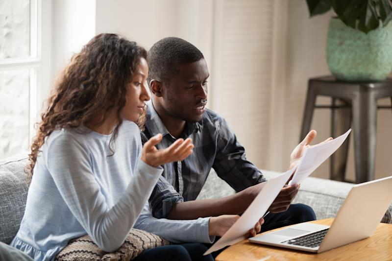 Concerned mixed race husband and wife take care of domestic bills reading papers at home, worried black couple consider bank documents, think of mortgage or loan, check paperwork together
