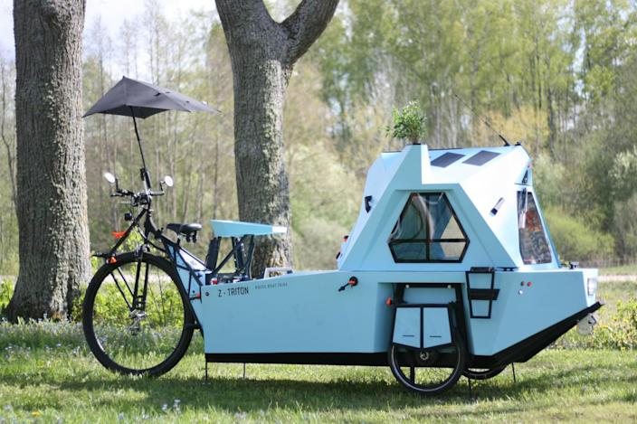 A protective umbrella pops up to protect whoever's pedaling the camper from the elements.