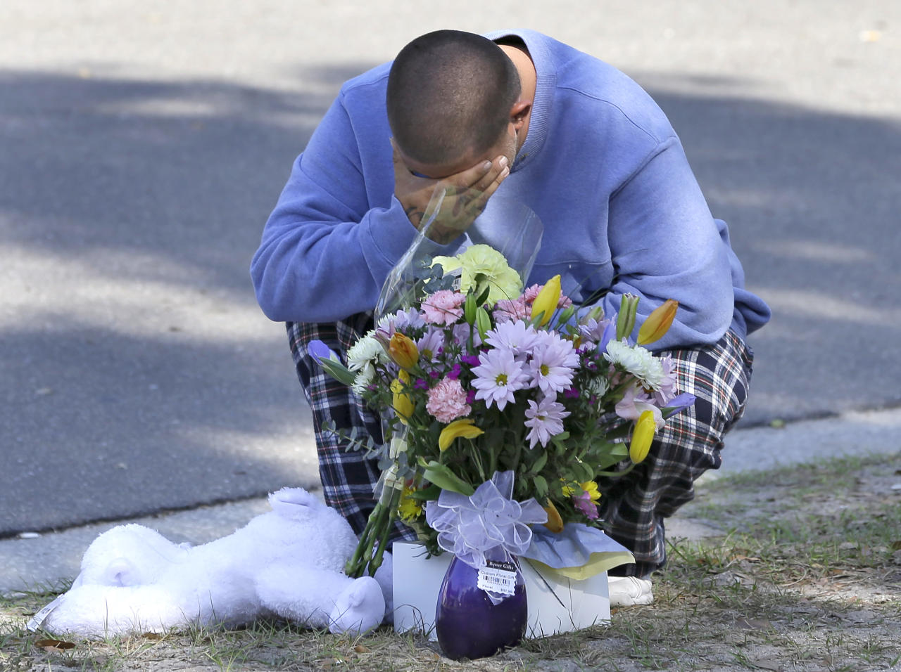 Jeremy Bush places flowers and a stuffed animal at a makeshift memorial in front of a home where a sinkhole opened up underneath a bedroom late Thursday evening and swallowed his brother Jeffrey in Seffner, Fla. on Saturday, March 2, 2013. Jeffrey Bush, 37, was in his bedroom Thursday night when the earth opened and took him and everything else in his room. Five other people were in the house but managed to escape unharmed. Bush's brother jumped into the hole to try to help, but he had to be rescued himself by a sheriff's deputy. (AP Photo/Chris O'Meara)