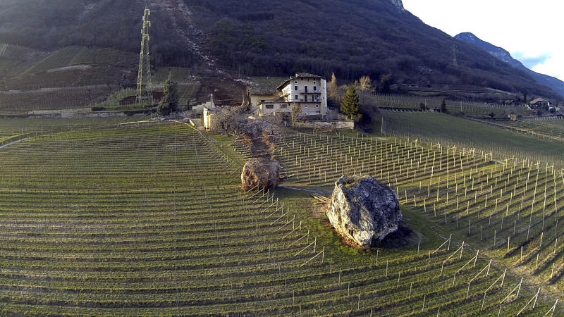 In this photo provided by Tareom.com Thursday, Jan. 30, 2014, and taken on Jan. 23, 2014, a huge boulder is seen after it missed a farm house by less than a meter, destroying the barn, and stopped in the vineyard, while a second giant boulder, which detached during the same landslide on Jan. 21, 2014, stopped next to the house, in Ronchi di Termeno, in Northern Italy. According to reports, the Trebo family living there was unharmed in the landslide. The boulder in foreground is from a much older landslide. (AP Photo/Markus Hell, Tareom.com, ho)