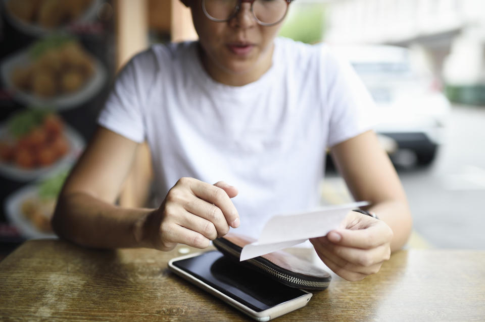 woman with receipt and mobile phone