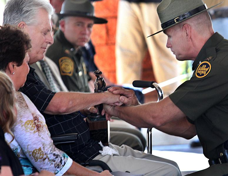 """Kent Terry Sr., father of Border Patrol Agent Brian Terry, and Richard """"Rick"""" Barlow, chief patrol agent of the Tucson sector, share a quiet moment during the dedication ceremony for a new station named after Brian Terry, Tuesday, Sept. 18, 2012 on Naco, Ariz. Brian was killed in a December 2010 firefight with bandits north of the Mexican border. Two guns found at the scene of the shootout were bought by a member of a gun smuggling ring that was being monitored in the government's botched gun smuggling probe known as Operation Fast and Furious. (AP Photo/Sierra Vista Herald, Beatrice Richardson)"""