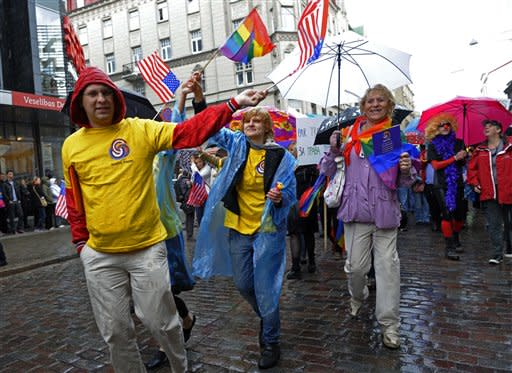 Participants in a gay pride parade march braving heavy rain in a street in downtown Riga, Latvia, Saturday, June 2, 2012. Several hundred activists from the Baltic states and neighboring countries braved rain and hail to participate in an annual parade in defense of gay and lesbian rights in Latvia. (AP Photo/Roman Koksarov)