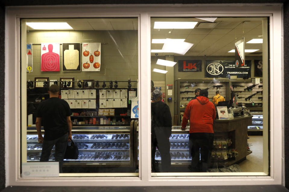 Customers stand inside the gun shop area of Maxon Shooter's Supplies and Indoor Range, as seen from the shooting range, Friday, April 30, 2021, in Des Plaines, Ill. After a year of pandemic lockdowns, mass shootings are back, but the guns never went away. As the U.S. inches toward a post-pandemic future, guns are arguably more present in the American psyche and more deeply embedded in American discourse than ever before. The past year's anxiety and loss fueled a rise in gun ownership across political and socio-economic lines. (AP Photo/Shafkat Anowar)