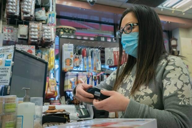 Lili Tran at the cash register inside Tap Phong Trading Co. The store plans to open Monday when some COVID-19 restrictions are lifted. (Sam Nar/CBC - image credit)