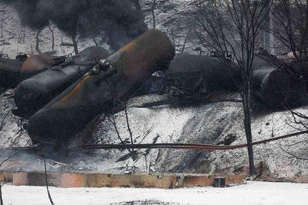 The charred remains of a house and a vehicle are shown below a derailed CSX Corp train in Mount Carbon, West Virginia, Tuesday, February 17, 2015. REUTERS/Marcus Constantino