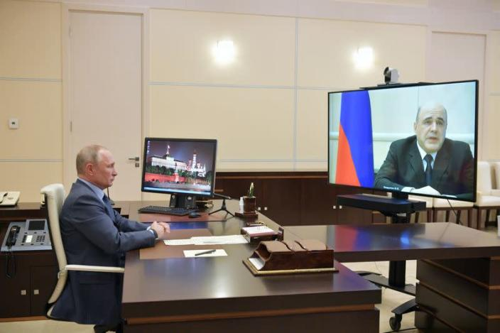 Russian President Vladimir Putin listens to Prime Minister Mikhail Mishustin during their meeting via a video link outside Moscow