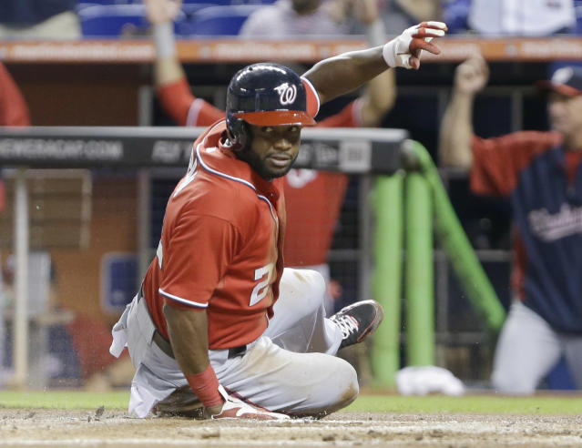 Washington Nationals' Denard Span looks back as he slides into home plate during the first inning of a baseball game against the Miami Marlins, Saturday, Sept. 7, 2013, in Miami. Span scored on a two-run home run by Ryan Zimmerman. (AP Photo/Wilfredo Lee)