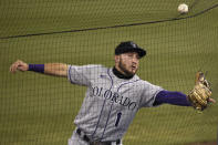 Colorado Rockies second baseman Garrett Hampson runs into the netting while playing a foul ball hit by Los Angeles Dodgers' Gavin Lux during the third inning of a baseball game in Los Angeles, Sunday, Sept. 6, 2020. (AP Photo/Kelvin Kuo)