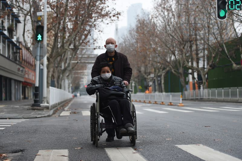 Man wearing a face mask pushes a woman on a wheelchair in Wuhan