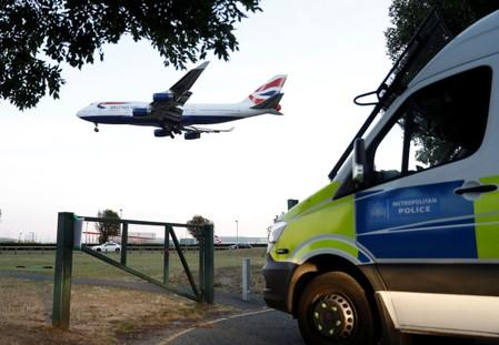 Police vehicles are seen parked near Heathrow airport after climate activists said they planned to fly drones near the airport, in London