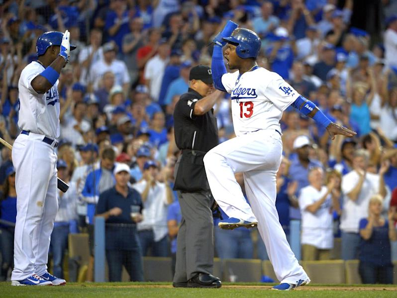 Los Angeles Dodgers' Hanley Ramirez (13), right, celebrates with teammate Yasiel Puig, left, after Ramirez scored on a single hit by Dodgers' Adrian Gonzalez in the third inning in Game 3 of the National League division baseball series against the Atlanta Braves, Sunday, Oct. 6, 2013, in Los Angeles. (AP Photo/Mark J. Terrill)
