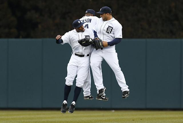 Detroit Tigers outfielders Rajai Davis, from left, Austin Jackson and Tyler Collins celebrate their 10-4 win over the Baltimore Orioles in a baseball game in Detroit Friday, April 4, 2014. (AP Photo/Paul Sancya)