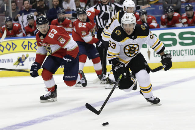 Boston Bruins left wing Brad Marchand (63) and Florida Panthers right wing Evgenii Dadonov, left, chase the puck during the second period of an NHL hockey game, Saturday, Dec. 14, 2019, in Sunrise, Fla. (AP Photo/Lynne Sladky)