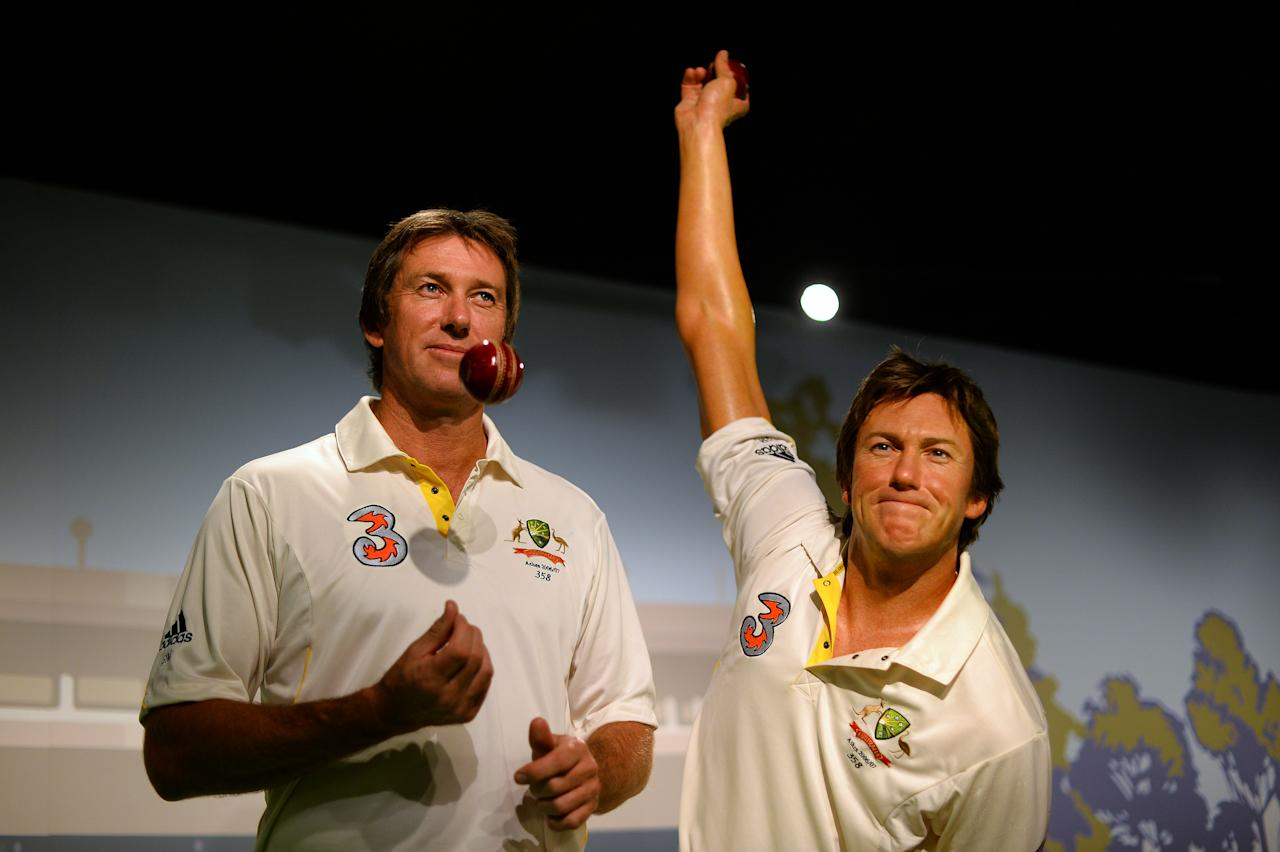 Australia's cricket legent Glenn McGrath (L) tosses a ball as he poses for photos during the launch of his wax figure at Madame Tussauds in Sydney on July 31, 2013. McGrath was the winner of the Madame Tussauds Sydney Aussie votes campaign where the Australian public was asked to cast their votes on which Australian sporting hero they wanted to see immortalised in wax.     AFP PHOTO / Saeed Khan        (Photo credit should read SAEED KHAN/AFP/Getty Images)