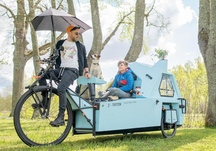 A father pedals the tricycle protion of the camper while his children enjoy the view from the cozier boat part.