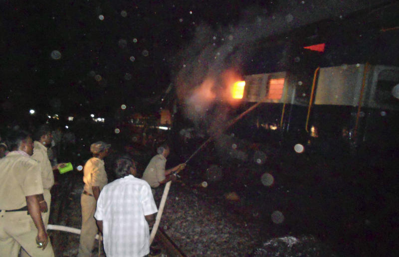 Firefighters and policemen try to douse flames on a train after an accident at a station near Penukonda, about 170 kilometers (105 miles) north of Bangalore, India, Tuesday, May 22, 2012. The passenger train rammed into a parked freight train and burst into flames before dawn Tuesday, killing more than a dozen people in southern India, officials said. (AP Photo)