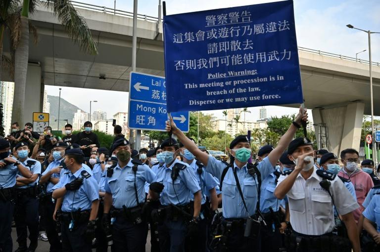 Hong Kong police held up banners warning pro-democracy activists outside the West Kowloon court in Hong Kong to disperse