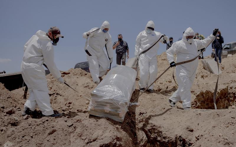 Gravediggers carry the casket of a person who died from the coronavirus at Municipal Cemetery No. 13 in Tijuana, Mexico - Bloomberg