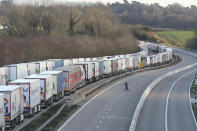 Freight lorries lined up on the M20 near Ashford, England, Friday Dec. 25 2020. Thousands wait to resume their journey across The Channel after the borders with France reopened. Trucks inched slowly past checkpoints in Dover and headed across the Channel to Calais on Thursday after France partially reopened its borders following a scare over a rapidly spreading new virus variant. (Gareth Fuller/PA via AP)