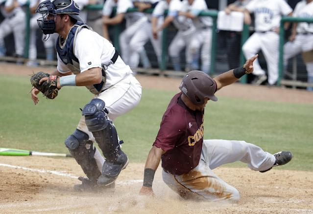 Bethune-Cookman's Josh Johnson, right, scores as Columbia catcher Mike Fischer, left, waits for the throw in the eighth inning during an NCAA college baseball regional tournament in Coral Gables, Fla., Saturday, May 31, 2014. Bethune-Cookman defeated Columbia 6-5. (AP Photo/Lynne Sladky)
