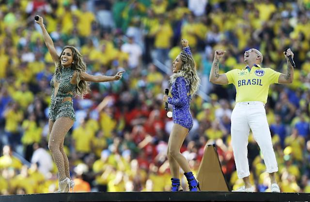 In this Thursday, June 12, 2014 photo, Jennifer Lopez, left, Brazilian singer Claudia Leitte and rapper Pitbull perform during the opening ceremony ahead of the group A World Cup soccer match between Brazil and Croatia, the opening game of the tournament, in the Itaquerao Stadium in Sao Paulo, Brazil. (AP Photo/Kirsty Wigglesworth)