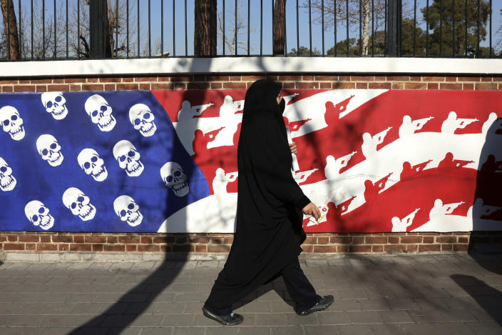 A mourner walk back from a funeral ceremony for Iranian Gen. Qassem Soleimani and his comrades, who were killed in Iraq in a U.S. drone attack on Friday, passing graffiti on the wall of the former U.S. Embassy in Tehran, Iran, Monday, Jan. 6, 2020. A push led by pro-Iran factions to oust U.S. troops from Iraq is gaining momentum, bolstered by a Parliament vote in favor of a bill calling on the the government to remove them. But the path forward is unclear. (AP Photo/Vahid Salemi)