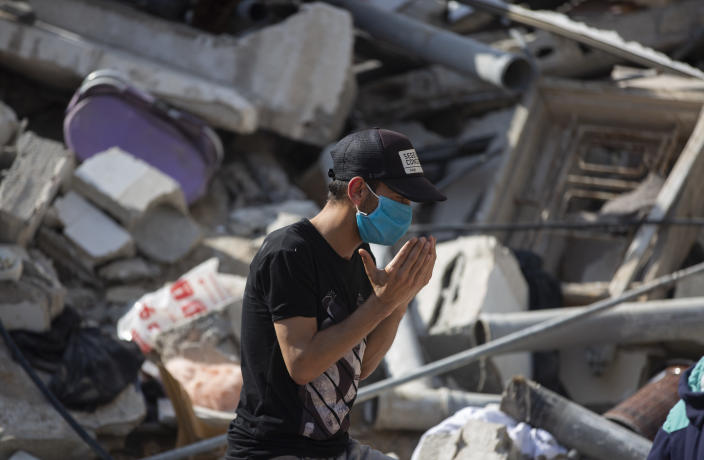 A Palestinian man prays as he stands amid the rubble of buildings destroyed in deadly Israeli airstrikes waiting for possible survivors to be rescued, in Gaza City, Sunday, May 16, 2021. Israeli airstrikes on Gaza City flattened three buildings and killed at least 26 people Sunday, medics said, making it the deadliest single attack since heavy fighting broke out between Israel and the territory's militant Hamas rulers nearly a week ago. (AP Photo/Khalil Hamra)